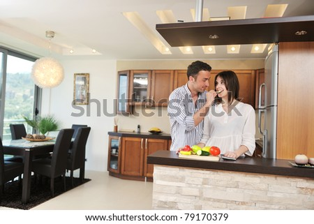 happy young couple have fun in modern wooden  kitchen indoor while preparing fresh food