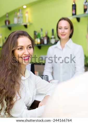 Happy young couple having a date with wine at bar. Focus on girl - stock photo