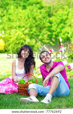 happy young couple having a picnic outdoor on a summer day looking up