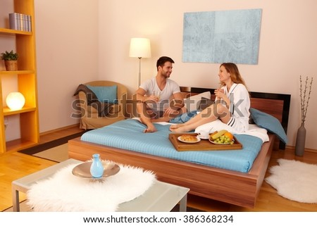 Happy young couple having breakfast in bed, having fun. - stock photo