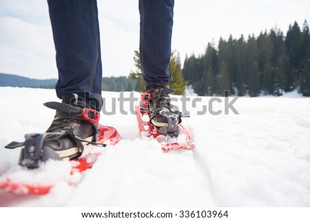 happy young  couple having fun and walking in snow shoes outdoor in nature at beautiful winter day. Health sport and relaxation - stock photo