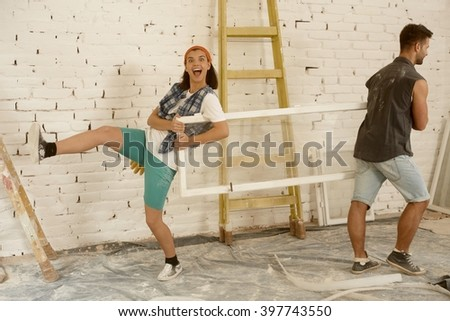 Happy young couple having fun at home renovation, holding window frame. - stock photo