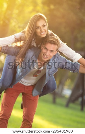 happy young couple having fun in sunny forest - stock photo