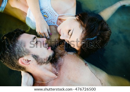 happy young couple having fun, man and woman in the sea on the beach. vintage retro style with soft focus and sun flare