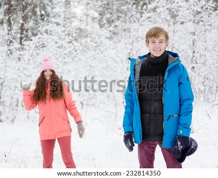 happy young couple having fun together in snow in winter woodland throwing snowballs - stock photo