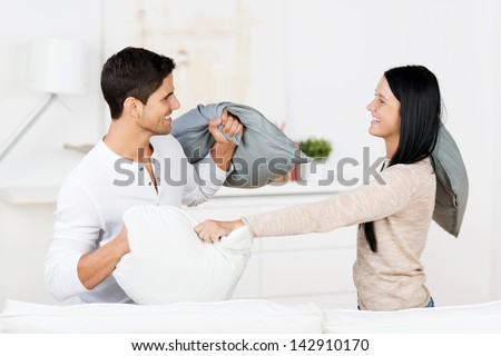 Happy young couple having pillow fight in house - stock photo