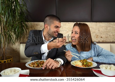 Happy young couple having romantic dinner at the Chinese restaurant - stock photo