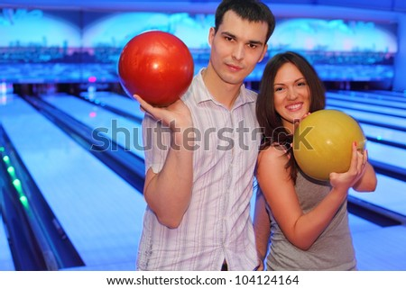 Happy young couple hold red and yellow balls in bowling club