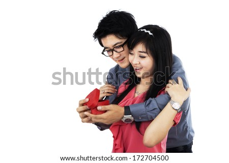 Happy young couple holding a valentine gift box - stock photo