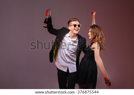 Happy young couple holding bottle of champagne and dancing over purple background - stock photo