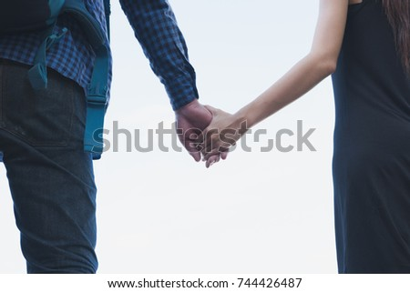 happy young couple holding hand. boyfriend and girlfriend walking togetheroutdoor in the park. love, relationship, romance concept