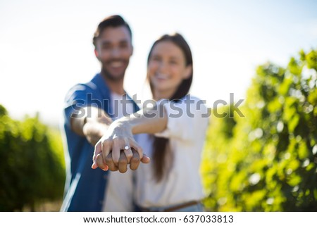 Happy young couple holding hands at vineyard on sunny day