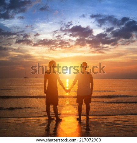 Happy young couple holding hands on sea beach during the beautiful sunset. - stock photo