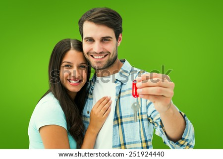 Happy young couple holding new house key against green vignette - stock photo
