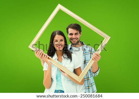 Happy young couple holding picture frame against green vignette - stock photo