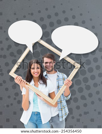 Happy young couple holding picture frame against grey - stock photo