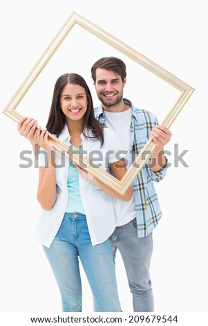 Happy young couple holding picture frame on white background - stock photo