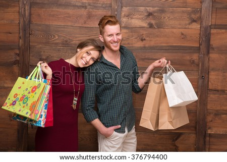 Happy young couple holding shopping bags with clothes. Man and woman like doing shopping on weekends.  - stock photo