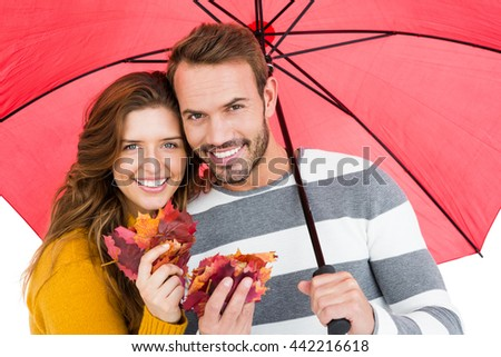 Happy young couple holding umbrella and maple leaves on white background - stock photo