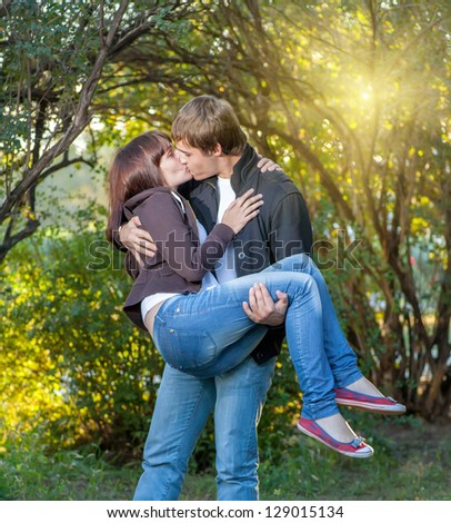 Happy young couple. Holding women on the hands and  fun a lot of positive emotions - stock photo