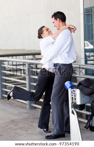 happy young couple hugging at airport - stock photo