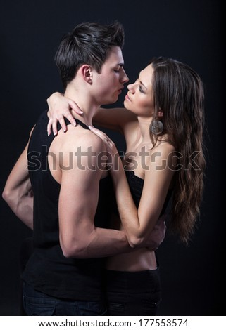 Happy young couple hugging. First love on dark background