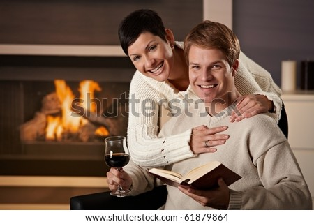 Happy young couple hugging in front of fireplace at home, looking at camera, smiling. - stock photo