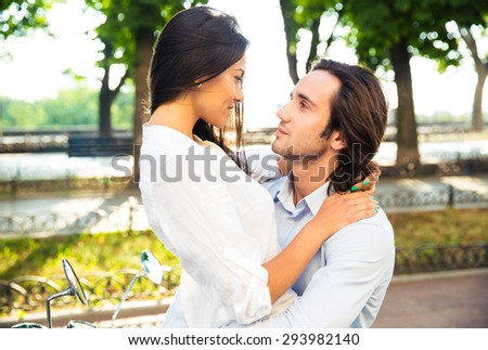 Happy young couple hugging outdoors and looking at each other - stock photo