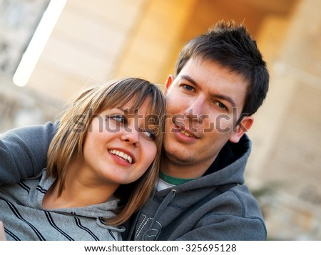Happy young couple hugging outdoors in a park