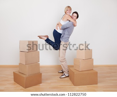 Happy young couple in a close ecstatic embrace smiling happily as they stand surrounded by cartons in their new home - stock photo