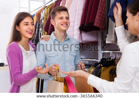 Happy young couple in a clothing store will consult with the seller