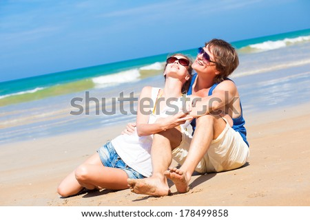 happy young couple in bright clothes in sunglasses