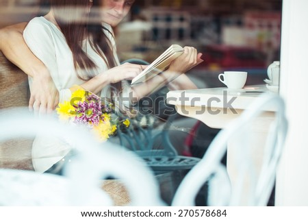 Happy young couple in cafe, having a great time together. View through cafe window. - stock photo