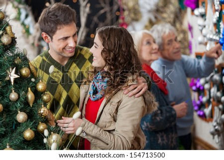 Happy young couple in Christmas store with parents shopping in background - stock photo