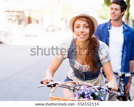 Happy young couple in city with bike - stock photo
