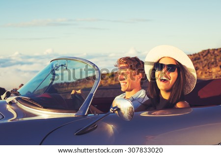 Happy Young Couple in Classic Vintage Sports Car at Sunset - stock photo