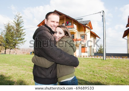 happy young couple in front of house