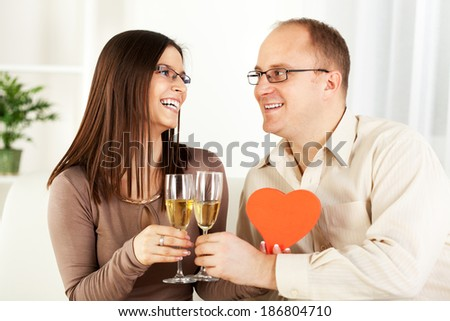 Happy Young couple in home interior enjoying in glass of champagne, with heart shaped box. The valentine's day. - stock photo