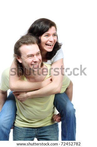 Happy young couple in jeans, funny girl jumps on boyfriend back and embrace him
