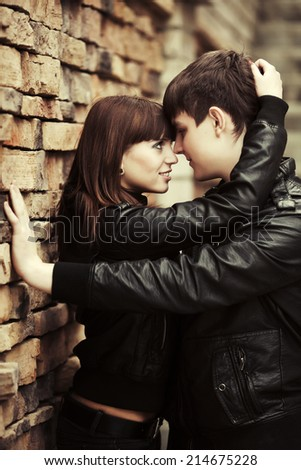 Happy young couple in love at the brick wall  - stock photo