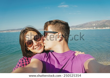 Happy young couple in love doing self-portrait on background of blue sea and man kissing a woman - stock photo