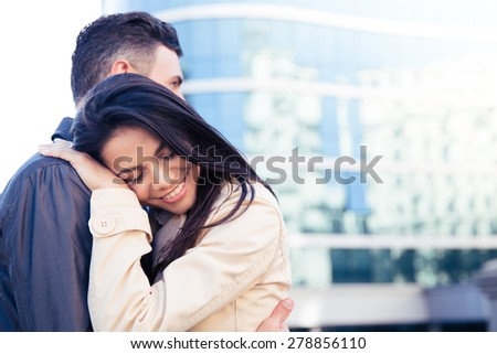 Happy young couple in love embracing outdoors - stock photo