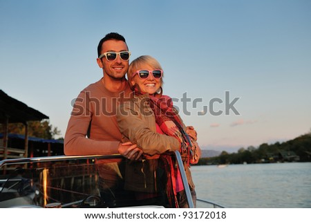 happy young couple in love  have romantic time at summer sunset   at ship boat while  representing urban and countryside fashin lifestyle - stock photo