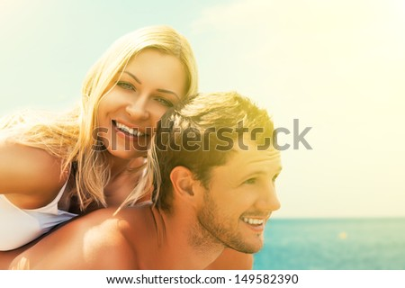 happy young couple in love hugging and laughing on the beach at Sea - stock photo