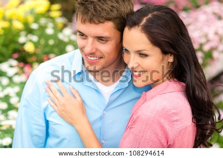 Happy young couple in love hugging in nature garden - stock photo