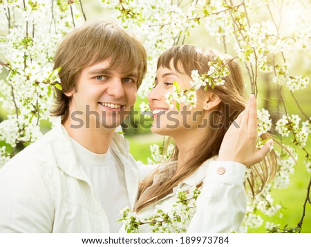 Happy young couple in love in a spring blossoming apple tree branches on a sunny day in the park.