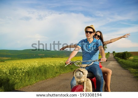Happy young couple in love on retro motorbike driving togetger and ejoying the trip in green field - stock photo