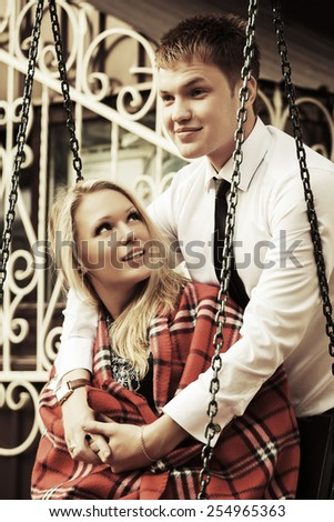 Happy young couple in love on the swing