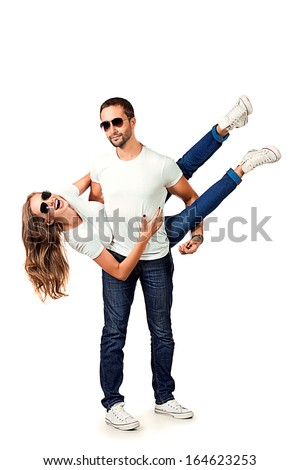 Happy young couple in love posing at studio. Isolated over white.