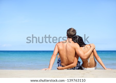 Happy young couple in love relaxing on beach vacation enjoying ocean view together sitting in the sand embracing and hugging. Beautiful young multiethnic couple, Asian woman, Caucasian man. - stock photo